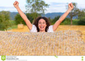 Main thumb excited young woman celebrating farm field standing behind round hay bale laughing cheering her hands raised 75213963